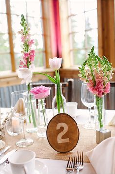 Wooden table numbers and single stem florals as table decor. Floral Design: Love This Day Events ---> http://www.weddingchicks.com/2014/05/29/rain-and-shine-rustic-colorado-wedding/
