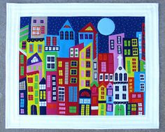 """""""Downtown"""" -   22 1/2 x 18 1/2 raw edged applique with the addition of 165 hand stitched windows to mimic panes of glass, a few french knots for architectural interest, and a 2 inch border to bring out the white."""