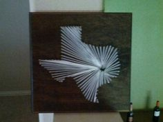 Nail and string Texas state on wood board