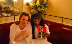 John gives book to Nile Rodgers