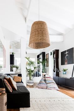 The living area in this converted shop have been styled simply with patterned cushions, wicker basket pendant light and an antique clock. Indoor palms add to the calm, relaxed style of the home. Photography: Maree Homer | Styling: Kayla Gex