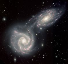 Like two skaters grabbing hands while passing, the two galaxies NGC 5427 (lower left) and its twin NGC 5426 (upper right), are beginning a collision that could take a hundred million years to complete. Already a bridge-like feature has begun to form between the galaxies. This intergalactic bridge acts like a feeding tube, allowing the twins to share gas and dust with one other across the 60,000 light years of space separating them.