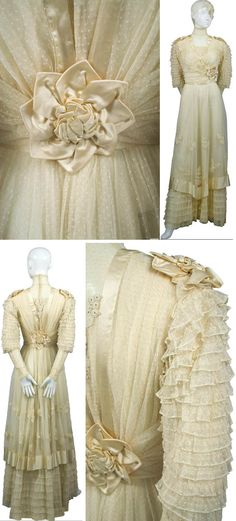 Edwardian-era wedding dress. Cream-colored dotted fine netting with lace appliqués, silk roses, and silk trim. Ruffled hemline and sleeves; lace appliqués throughout. Lined in silk; closes with hooks & eyes in the back. DressingVintage.com