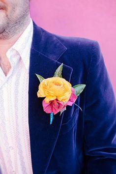 Bright orange boutonniere pinned to a mod-styled groom's purple velvet lapel | Photo by Ashley Williams | Event design by The Dainty Lion | Floral design by Compass Floral