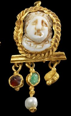 A bow earring with a cameo showing a Medusa  with glass stones, pearl, Roman 2nd century A.D.