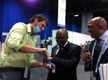 """South African Minister of Health getting """"Stop TB/HIV"""" temporary tattoo applied at World AIDS Conference 2012 in Washington, DC following """"Tuberculosis & HIV: Protecting the Vulnerable"""" talk show on 22 July 2012."""