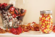Cute little touches like this jar of candy corn make the party. You can even make multiple ones to send home with your guests as party favors! #partycrafters #fall #harvest