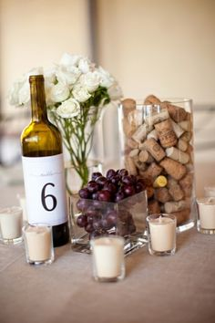 Wine bottle with table number, flowers, cork-filled vase and some grapes