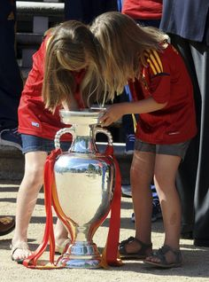 Spain's Infantas Sofia (R) and Leonor put their arms into the Euro 2012 trophy during a visit of the national soccer team members to Madrid's Zarzuela Palace a day after their victory at the Euro 2012, July 2, 2012.