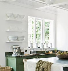 """A collection of white crockery displayed on open shelves against a white wall become an """"art opportunity"""" in this cottage kitchen. myhomeideas.com"""