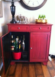 I love this little thrift store cabinet turned bar, refinished with red stain