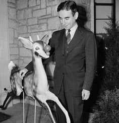 Robert May, the man who wrote the story of Rudolph the Red Nosed Reindeer in 1939, stands in front of his home in Skokie, IL with his Rudolph creation on December, 19, 1949. May wrote the story, at the request of his boss, to hand out as a promotional item to customer's that came into the Montgomery Wards stores that year.
