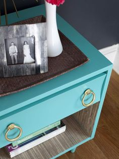 A made over vintage nightstand, painted turquoise with gold accents and a grasscloth-covered interior.