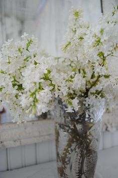 white lilac gathered on mass in clear vase. so simple & pretty