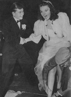 Judy Garland places her footprints in cement outside Grauman's Chinese Theatre with Mickey Rooney 1939 | Tumblr