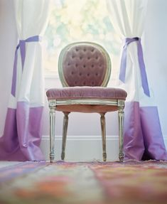 A tufted French side chair sits in front of a window, flanked by white-and-purple silk drapes.