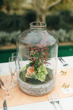 floral centerpiece under a glass jar, photo by Sunny 16 Photography http://ruffledblog.com/modern-austin-wedding-with-a-playful-twist #weddingideas #centerpieces