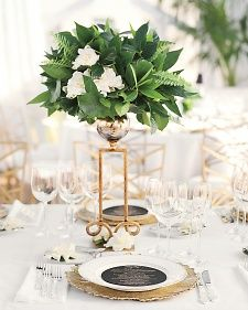 Wavy gold glass chargers and tall, scroll-like vessels of gardenias and ferns gave the white tables a dash of Art Deco glamour.