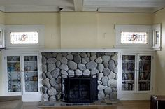 windows over bookcases flanking fireplace (what is with the river rock?! Eeek! Someone needs some plaster, fast)