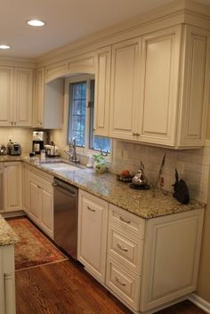 white kitchen cabinets with a glaze, granite counters, and subway tile back splash.