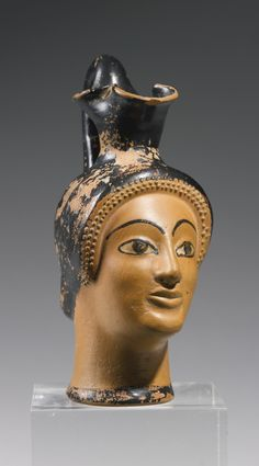 AN ATTIC POTTERY OINOCHOE, COOK CLASS, CIRCA EARLY 5TH CENTURY B.C. with trefoil mouth and high cylindrical handle, the body in the form a woman's head with finely painted eyes and eyebrows, the hair with applied gesso curls framing the forehead and temples.  Height 5 5/16 in. 13.5 cm