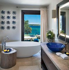 A bath opens onto a deck with breathtaking views of the water.  Hotel Pitrizzia Sardinia Italy