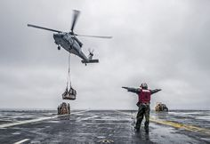 "PACIFIC OCEAN (May 30, 2014) Aviation Ordnanceman Airman Alexander Wagner, from Galva, Ill., signals the pilot of an MH-60S Seahawk from the ""Island Knights"" of Helicopter Sea Combat Squadron (HSC) 25 during an replenishment-at-sea between the U.S. Navy's forward-deployed aircraft carrier USS George Washington (CVN 73) and Military Sealift Command dry cargo and ammunition ship USNS Washington Chambers (T-AKE 11). (U.S. Navy photo by Mass Communication Specialist 3rd Chris Cavagnaro/RELEASED)"