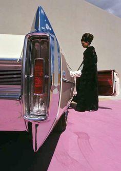 Model wearing mink coat by Emeric Partos entering a 1965 Cadillac Coupe de Ville, 1964.