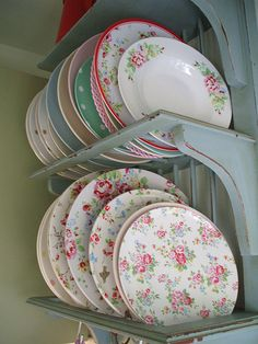 Pretty array of vintage plates displayed on blue open shelves in kitchen
