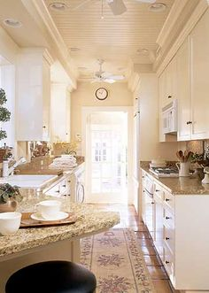 White cabinets and appliances open up a small space, which is perfect for smaller layout such as a galley-style kitchen. In this kitchen, an angled dishwasher near the sink forms a mini peninsula, introducing a welcome diagonal into the narrow kitchen space. #kitchen #whitecabinets