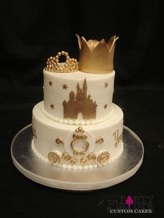 White buttercream base, pearl border, gold fondant stars, castle and carriage. Topped with fondant crown and tiara.