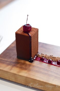 My take on this Plating:  Black Forest Cake or Cheesecake cut with cookie cutter, rolled in powdered chocolate. Streak of raspberry (sauce, coulis).