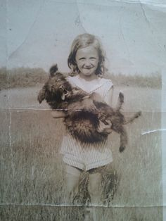 Vintage photo, squinting girl carrying dog