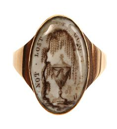 A gold and enamel mourning ring, c.1760-1820, featuring a weeping willow, symbol of mourning, and urn, symbol of death, and the words 'NOT LOST BUT GONE BEFORE'.