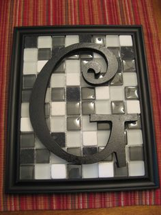 Leftover frame from our daughter's wedding, glass tiles from Home Depot, letter we spray painted black from Hobby Lobby.  Viola!