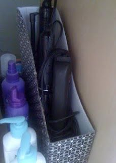 Simple Storage for the Bathroom: Use a magazine holder for storing curling irons and flat irons under the sink