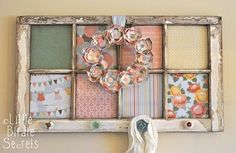 A repurposed old window frame turned into a lovely wall piece with cute wall/wrapping paper cut outs where the glass used to be and pretty doorknobs for hanging up your pretty things. A little bit of shabby and a whole lot of chic!! I love upcycling!  Click if you want to learn how this was made.