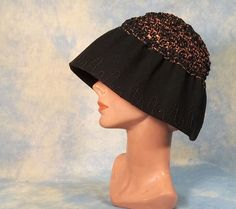 A classic 1920s black felt deep cloche vintage hat with a loosely woven crown made from a heavy black yarn like fibre and metallic thread. The crown is very stretchy and airy from the very open weave, a rather unique style that has that wonderfully deep shape the covers up much of the face