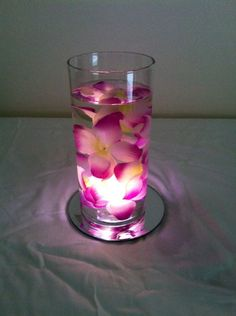 Great centerpiece idea! These were super inexpensive & quick to make. The glass vases, mirrors and flowers were all purchased from the Dollar Tree for $1 each. The flowers actually came off a Hawaiian Lei that was took apart. And the lighting is a submersible led light. Just place the light in the vase, add water and then place the flowers in the water.