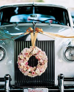 A 1950s Roll-Royce's hood is draped with ribbon that suspends a wreath of roses.