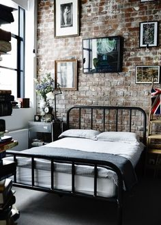 cool old bed against brick wall-add framed pics-looks nice