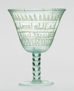 """Goblet, 9th century  Western Asia or Egypt  Transparent pale greenish blue glass, blown from two gathers and scratch-engraved  H. 4 3/4 in. (11.9 cm), Diam. 3 5/8 in. (9.2 cm)  Inscription (in kufic script): """"Blessings from Allah to the owner of the goblet. Drink!"""""""
