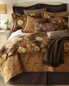 """This is a grown up casual bedroom vignette.  The white wall, headboard and parsons table keep things fresh and modern, while the dark euro shams and skirt excite the eye by adding contrast.  Although some florals are used, the mix of patterns and brown tones keep the vignette from being """"girly"""".    """"Ballad Bouquet"""" Bed Linens by Legacy Home at Horchow."""