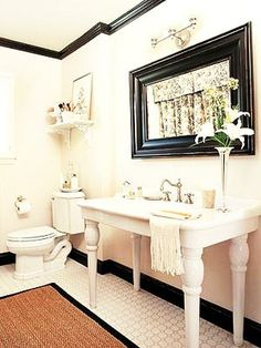 What a cute bathroom..I LOVE the simplicity of this space with the black & white colors..I especially LOVE the black crown molding & the black baseboards against all the white!!!! <3
