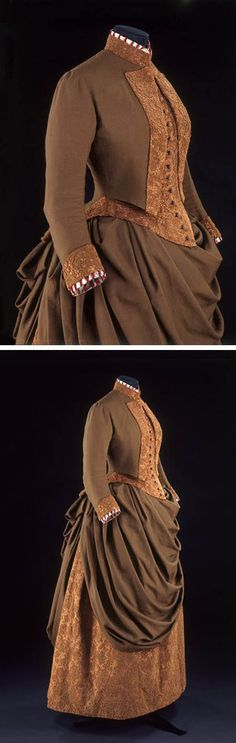Walking dress, Mme. Cridon, Paris, 1885. Wool & silk. Bodice has opening in front to reveal underbodice resembling a man's waistcoat, which is attached to the outer jacket at side seam. Bustle skirt with draped overskirt; steel hoops & tapes in back of underskirt to pull it into shape over bustle pad. Hem reaches top of wearer's shoes, making it easier to walk in than a trained skirt. Victoria & Albert Museum
