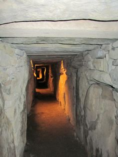 NEWGRANGE is a prehistoric monument in County Meath, Ireland, about one kilometre north of the River Boyne. It was built about 3200 BC, during the Neolithic period, which makes it older than Stonehenge and the Egyptian pyramids. Newgrange is a large circular mound with a stone passageway and chambers inside. The mound has a retaining wall at the front and is ringed by 'kerbstones' engraved with artwork.