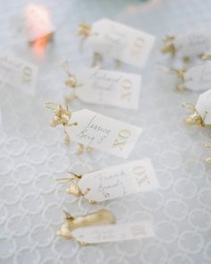 For these escort cards, tags from Sugar Paper were tied to whimsical animal figurines that the couple covered with gold paint.
