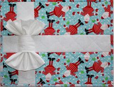 """Presently Wrapped Christmas Placemats and Napkins make the perfect holiday place setting. Make them in sets for gifts, too. Very easy fusible applique--you can make a set in an afternoon, using fabric you quilt yourself following the directions or you can substitute pre-quilted double-layer fabric or even readymade quilted mats and add the """"ribbon and bows."""" Easy any way you do it. Get the pattern at www.craftsy.com"""