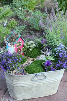 Plant a fairy garden in an old washtub, birdbath or wagon. On my to-do list- I've seen somewhere where they use recycled bottles to make fairy houses this could be cute too. Love the fences in this one.
