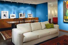 Dramatic pendant lighting creates an airy effect in a modern living area. | Blueberry (26-16), @prattandlambert